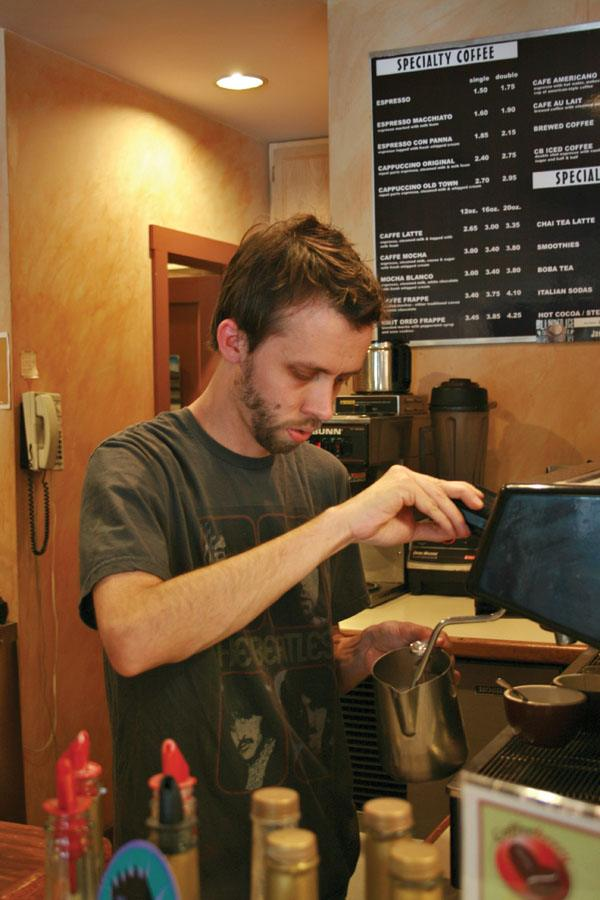 Coffeeberry manager Nick Tondee steams milk while preparing a latte for a customer. / photo by Courtney Droke