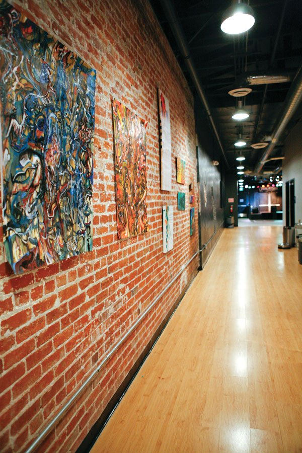 Every month The Wire features art on an empty brick wall in the entrance of the building. The owners decided that they could help local artists while filling up an empty wall. David Ward, an art student at Cal Poly Pomona, hung two of his paintings for the April gallery. / photo by Rhiannon Mim