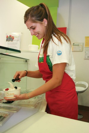Preparing a large frozen yogurt for a customer, University of La Verne student Ashly Gillis adds raspberries and blackberries to the low-calorie snack. O-lime is open Monday through Saturday from 11:30 a.m. to 10 p.m. and Sunday from 11:30 a.m. to 9:30 p.m. / photo by Courtney Droke