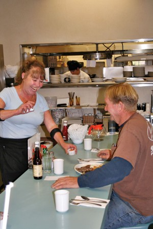 """Mona Shumate (""""Mona from Pomona"""") shares a laugh with Jim Beckman, a Village Inn regular, while serving him breakfast at the coffee bar. Beckman stops by the Village Inn at least once a week for breakfast. / photo by Lauren Pollard"""