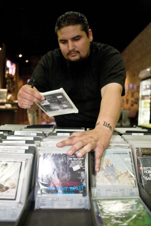 Employee Brian Ortiz checks the stock at the Glass House Record Store. The store hosts free musical performances on the second Saturday of every month during the Downtown Art Walk. / photo by Rhiannon Mim