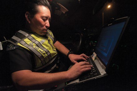 La Verne officer Robert Nishimura uses both his in-car computer and the police band radio to check the status of drivers' licenses and vehicle registrations in the DMV archives. / photo by Warren Bessant