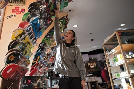 Luke Schlum, who made the transition from eager young customer to La Verne sales associate, reaches for one of more than 100 brands of skateboard decks. / photo by Garrett Gutierrez