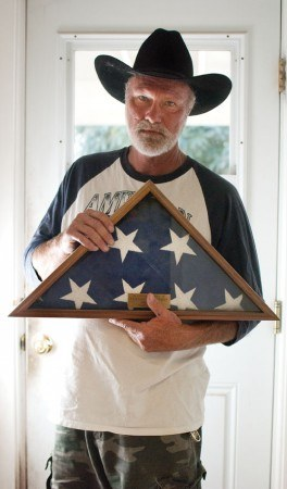 Proudly holding the flag that graced his father's funeral, Tim Morrison is reminded of his father's tribute to America while serving as a Marine Sergeant fighting in WWII. Tim displays his father's flag in his home's front window.
