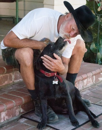 Shared love passes between Tim Morrison and Bubba, Tim's constant companion, at his Third Street La Verne home. / photo by Candice Salazar
