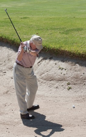 Patt Masson of Claremont attempts to hit the ball from the bunker and onto the green. Masson, who learned to play golf in Ireland, has been playing Marshall Canyon's course since it opened in 1966. / photo by Cassandra Egan