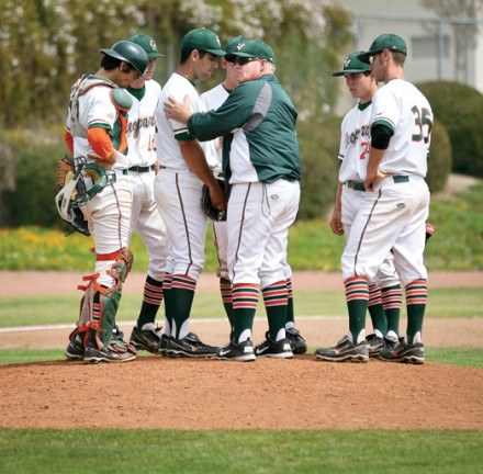 La Verne Head Coach Scott  Winterburn offers encouragement to pitcher Javi Iniguez, with infield players gathering around to assess the current game situation, during a meeting at the mound in the midst of a tense game against Claremont McKenna College. The coach frequents the mound during games to make sure his players are on track for a win. / photo by Mitchell Aleman