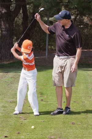 Golf pro Kenny Murray helps  8-year-old Matthew Ibarra with his backswing at the Marshall Canyon Golf Course range.  Kenny has coached both Matthew and his older brother Julio Ibarra for about a year. / photo by Cassandra Egan