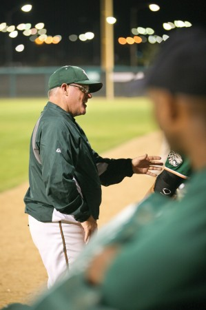 Head Coach Scott Winterburn takes to the front of the dugout to instruct his Leopard baseball players on how to turn the game's momentum in their favor. / photo by Mitchell Aleman