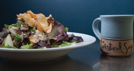 This Granny Smith Apple and Goat Cheese Salad includes julienned chicken breast, granny smith apples, candied pecans, apple chips, and mixed greens tossed in champagne vinaigrette topped with goat cheese. The coffee mugs have all been handmade by Jolyn's mother Jennifer Simison. / photo by Katherine Careaga
