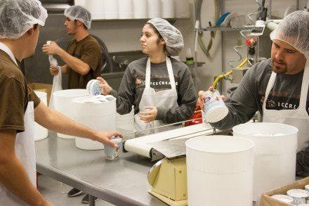 Dr. Bob's Handcrafted Ice Creams' employees Brianda Salcedo and Eddie Perez, put lids onto the freshly filled cartons of ice cream before Josh Sandoval places them onto a conveyor to be sent through a machine for freezing.  / photo by Ryan Gann