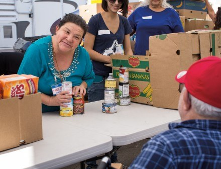 Yaneth Guzman, distributing food, has been volunteering at the Sowing Seeds for Life food bank for two years. Guzman says she volunteers at other similar organizations in many of the surrounding cities. / photo by Nicole Ambrose