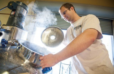University of La Verne alumnus Michael Kress graduated with a chemistry degree in 2010 and now is one of the main brewers for the La Verne Brewing Company. Kress spends his weekend mornings, beginning as early as 6 a.m. in the brewery perfecting the production of the beer. Kress tends to the seven-barrel brewing system to make sure the beer is not overheating. / photo by Hunter Cole