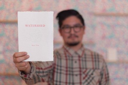"Devon Tsuno holds up his art exhibit program within the Weingart Center for Liberal Arts building. The wallpaper behind him is one of his main pieces that explains his theme ""Watershed."" / photo by Keenan Gilson"