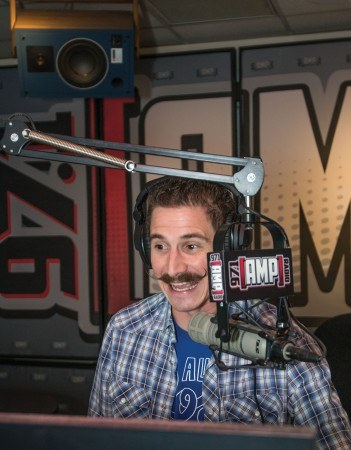 Kevin Schatz introduces an upcoming song on 97.1 Amp Radio. While listeners can not see his iconic moustache, many have become aware of it through Schatz's comedy videos, which are posted on Amp's website. / photo by Daniel Hargis