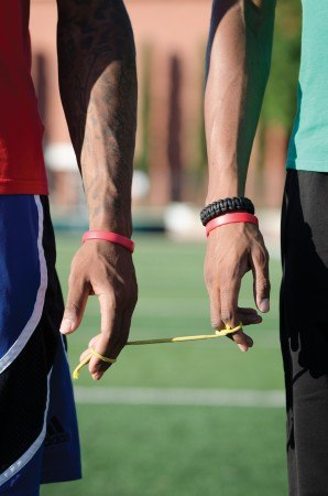 Guide-runner Chancise Watkins' fingers are tied to senior University of La Verne Track and Field teammate James Francis by a simple string. The string enables the blind runner to match the stride of the guide runner. / photo by Emily Bieker
