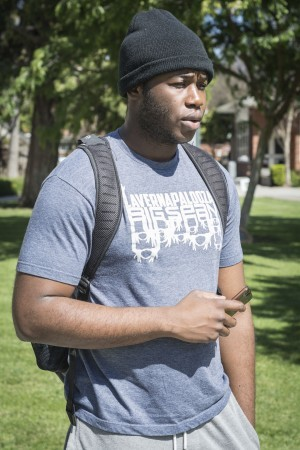 Junior chemistry major Bryan Okereke uses his cellphone between classes to keep himself busy, but also to keep in touch with his football teammates and coaches. / photo by Daniel Torres