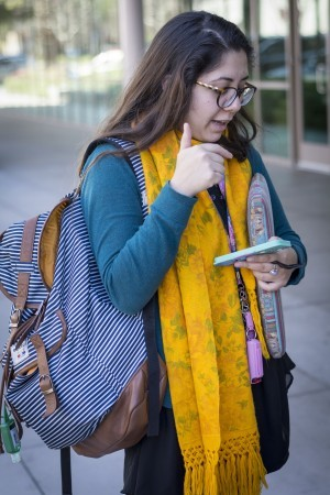 Jacqueline Pimental, a junior creative writing major, explains how she uses her smartphone throughout the day. Although she finds herself using her phone frequently, she makes sure to put it away when she spends time with her friends and family. / photo by Daniel Torres