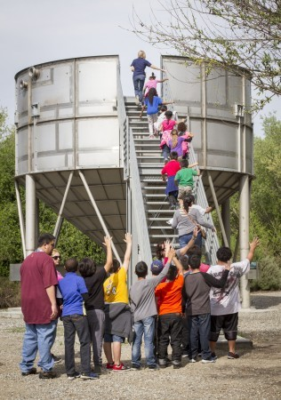 Michelle O'Brien leads a group up the observation tower to get a wide view of the park. The students of Juniper Elementary School in Fontana came to learn about water and wildlife at Chino Creek. / photo by Celine Dehban