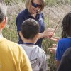 Michelle O'Brien gives each student a piece of a cattail to feel its fluffy texture. O'Brien explained that the cattails are important to water preservation because they clean water by filtering out nitrogen, phosphorous and other pollutants. / photo by Celine Dehban