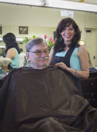 Delia Heredia, owner of Delia's Barbershop, welcomes each one of her customers with a smile. For 15 years, Gerald Parker has been a loyal client. Every customer leaves with a stylish cut, a good story and a good laugh. / photo by Michelle Leon