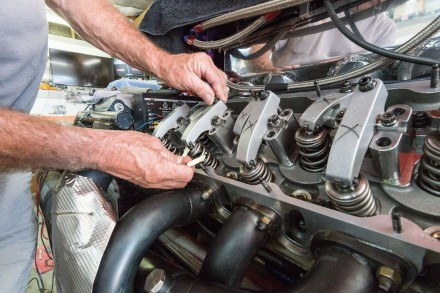Dave Isley uses a feeler gauge to check and adjust the valve lash, or the clearance between the rocker and the tip of the exhaust valve. The rockers open and close the fuel intake and exhaust valves, and when out of adjustment, they hit and cause damage. / photo by Helen Arase