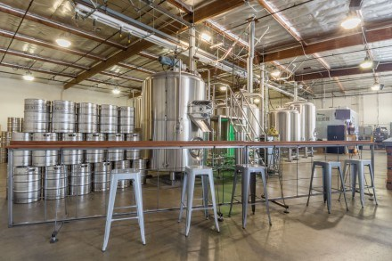 The tasting room of the Old Stump Brewing Company is an open area equipped with board games and a full view of the brewery tanks. These tanks are used weekly to make new batches of beer. / photo by Kathleen Arellano