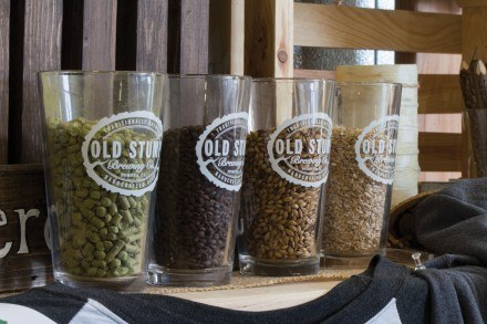 Grains are displayed next to Old Stump's merchandise to show a few of the main ingredients the company uses in its craft beer. / photo by Kathleen Arellano