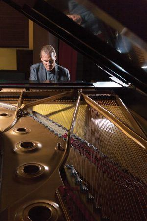 """Reed Gratz, department chair and professor of music, improvises on the Steinway and Sons grand piano on the Morgan Auditorium stage. In his 40th year as an educator at the University of La Verne, Reed concentrates in jazz music, from teaching jazz history to playing it with his band, the """"Reed Gratz Band."""" / photo by Kathleen Arellano"""