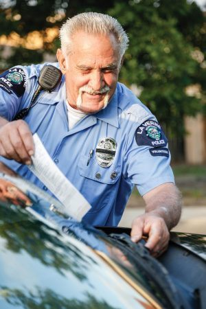 Dave Boscarino, a city of La Verne retired senior volunteer patrol officer, slips a citation into the window of a parked car after his partner Norm Faustini fills out the date, location and vehicle information. While on patrol, members of the RSVP pay close attention to parked cars to make sure registrations are up to date. If not, they will issue a citation, one of the many enforcement powers RSVP officers hold. / photo by Amanda Duvall
