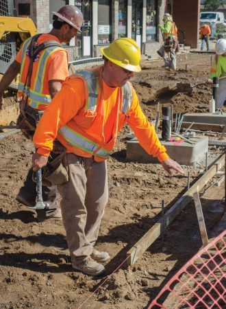 Construction worker Scott Hemming builds forms to pour concrete for the new sidewalks. The cement sidewalks replace the 1970 era boardwalks and symbolize a thematic change for the city of San Dimas. / photo by Sarah VanderZon