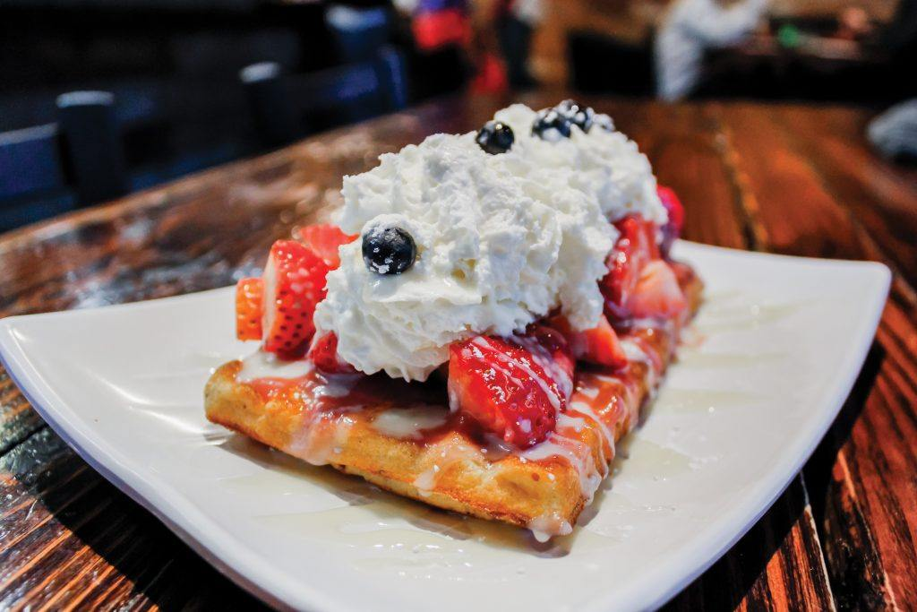 "The 'Merica Waffle is covered in sweet and juicy strawberries and blueberries, topped with whipped cream. It shows off thematic red, white and blue colors. The 'Merica is one of nine signature sweet dishes offered at Wähfles Café, located near the intersection of Foothill Boulevard and Wheeler Avenue in La Verne. ""The vision for Wähfles has always been to be a community based center, to provide humble service, good food and to connect with people,"" Brown explains. ""If you want to stay here for six hours, great. If you want to get a coffee to go, great. We just really want to be a community based center."" / photo by Tyler Deacy"