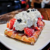 "The 'Merica Waffle is covered in sweet and juicy strawberries and blueberries, topped with whipped cream. It shows off thematic red, white and blue colors. The 'Merica is one of nine signature sweet dishes offered at Wähfles Café, located near the intersection of Foothill Boulevard and Wheeler Avenue in La Verne.""The vision for Wähfles has always been to be a community based center, to provide humble service, good food and to connect with people,"" Brown explains. ""If you want to stay here for six hours, great. If you want to get a coffee to go, great. We just really want to be a community based center."" / photo by Tyler Deacy"