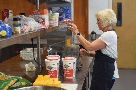 Ellen Weaver, Church of the Brethren volunteer, preps the ingredients to cook for the Food Network dinner. / photo by Nadira Fatah