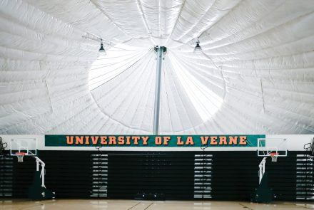 "Concrete foundations support the large steel posts that hold up the peaks of the Teflon fabric; the base of the building consists of ceramic blocks. The upstairs gym floor provides La Verne teams with a home field advantage as a result of its unique dimensions. ""There certainly is a home court advantage for basketball and volleyball. There is no background, so judging distance is somewhat difficult until you get used to it. Also, the rubberized surface is very different from other courts,"" says Rex Huigens, professor of kinesiology emeritus. / photo by Cierra Boess"