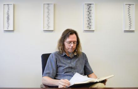 In a conference room on the third floor of Founders Hall, David Chappell's generative art prints hang framed. The prints are computer renderings based on his research of sinuous meander patterns, which were inspired by the organic flowing curves of meandering streams. David's published paper about the patterns was featured in 2015 on the front cover of the Journal of Mathematics and the Arts. / photo by Audrey Gaudette