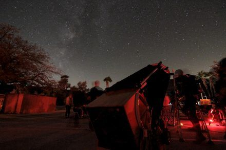 Jeff Kaufman aims his camera into the night sky to capture images of deep sky objects at the Nightfall Star Party at Borrego Springs, California. Jeff's computer is connected to a specially built camera that compiles three exposures sensitized for red, green and blue to create a color image. The computer is also used to aim and operate the apparatus to his left, which tracks his camera in the night sky. Also pictured is Jose Magsaysay's telescope, the largest at the event. / photo by Spencer Croce