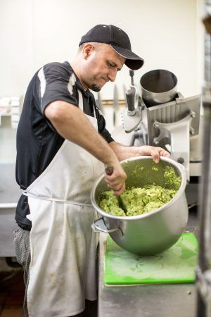 Benie Tapia hand mixes a bowl of avocado into guacamole, a La Paloma staple. Guacamole is usually paired with tacos and tostadas. / photo by Taylor Griffith