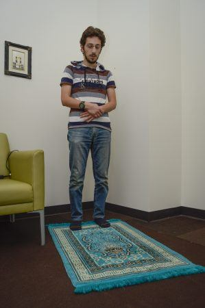 Firas Arodaki's bright blue prayer rug is pointed northeast in the Qibla direction toward Mecca during his daily prayers in the prayer and meditation room on the second floor of the Campus Center. When Firas co-founded the Muslim Student Association  in 2010, he petitioned the University of La Verne administration to install a prayer room on campus. / photo by Claudia Ceja