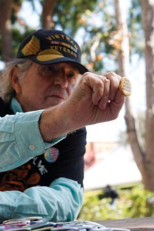 """Dan Kennan owns four shoeboxes full of buttons from every march, demonstration and protest event he has attended. His shirt reads, """"Vietnam didn't kill me. But the Agent Orange sure is trying to."""" / photo by Celeste Drake"""