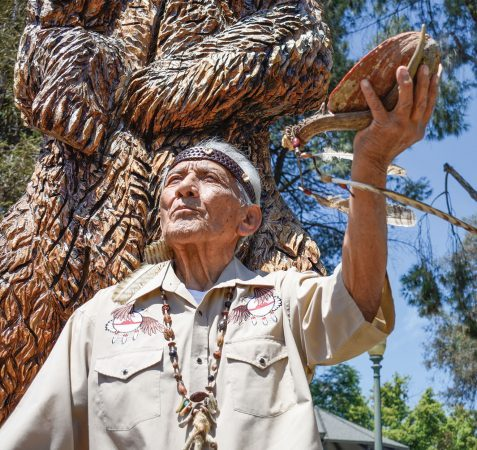 "Ernest ""Ernie"" Perez Teutimez Salas, chief and spiritual leader of the Kizh tribe, blesses the bear  wood carving in Pomona's Ganesha Park with a short prayer and burning sage in an abalone shell perched  on a deer antler. / photo by Natasha Brennan"