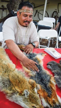 Kizh Tribe member Armando Campos explains to children at the Homestead Museum why coyote and fox pelts were important to the tribe. / photo by Natasha Brennan