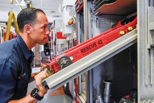 "Andre Flores, firefighter, paramedic and association member, removes a ladder from the quint and reviews its equipment: ladders, hoses, carry axes, crowbars, electric saws and the Jaws of Life. The term ""quint"" refers to the five functions the truck provides: pump, water tank, fire hose, aerial device and ground ladders. At each shift change, the firefighters bring out the vehicles to make sure all equipment is functioning and accounted for. / photo by Janelle Kluz"