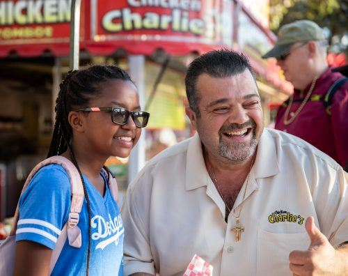 Charlie Boghosian and Pomona resident Anastacia Singletary snap a photo in front of his booth at the L.A. County Fair. As a leader in the fair food industry, Charlie is a fair celebrity, and his exotic food restaurants are destination sites. / photo by Jaren Cyrus