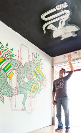 "Jason Lamotte, former resident director of visual art at the dA Center, added an installation to the entrance to create mural space for the ""d'Aztlan: Aztlanization–Past, Present, and Future"" show. ""The dA to me is like a life raft or plane, and I don't know if it's going to sink or crash because people don't know about it or the funding. But it just keeps opening doors to new creative work,"" Jason says. / photo by Natasha Brennan"