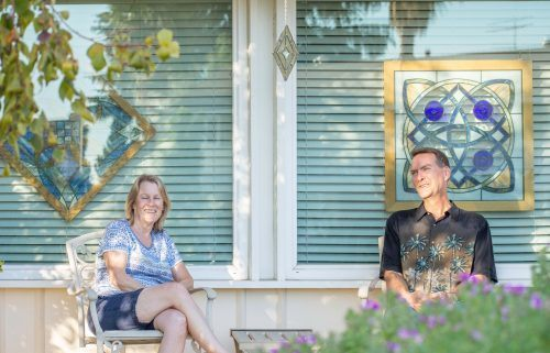 The sunlight dances on three pieces of stained glass art behind Mark and Julie Nelson. Mark creates many of the prize winning glass art pieces with  assistance from Julie, who helps him select glass  colors that symbolize the meaning behind his art. / photo by Kayla Salas
