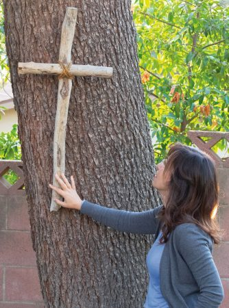 Julie AbiGhanem feels the rustic cross in her backyard from an antique store in Morro Bay. Christianity was an outlet for her growing up, and she believes God was the one protecting her through every tribulation she experienced. / photo by Layla Abbas