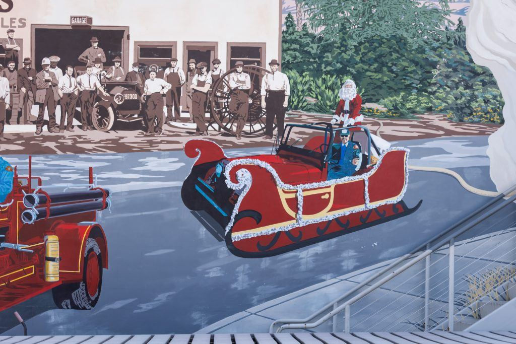 The mural's Santa sleigh, which represents a 93-year tradition of the fire fighters passing out candy to the children of the community on Christmas day stirs controversy with present day firefighters. / photo by Kayla Salas