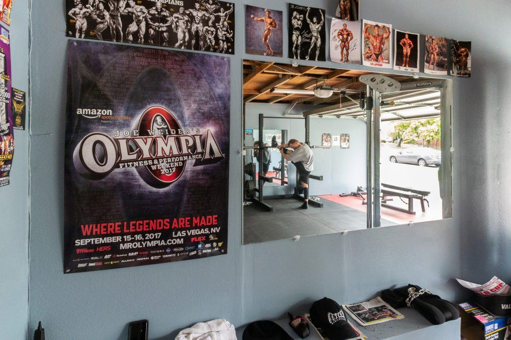 Loren Dyck warms up at his home gym surrounded by athletic machines and signed posters from competitions in which he has participated. He has several mirrors not only to watch his form but also because body building is an aesthetic sport. / photo by Molly Garry