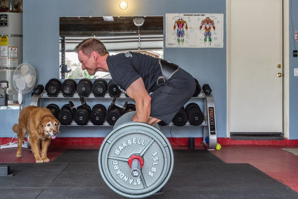 Loren Dyck, University of La Verne professor of management, dead lifts 315 pounds while his dog Max watches. Throughout his workout, Loren adds more weight and performs fewer reps. / photo by Molly Garry